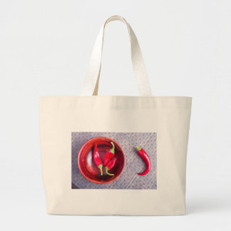 Red raw pepper in a brown wooden bowl large tote bag