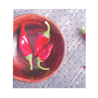 Red raw pepper in a brown wooden bowl notepads