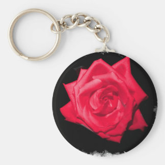Red rose bloom against a black jagged backdrop keychains