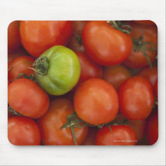 red tomatoes with one green one for sale at the mouse pad