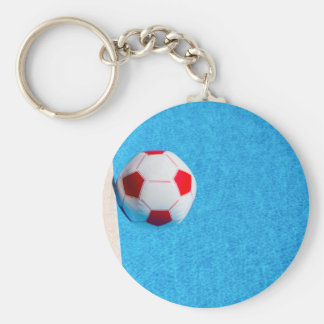 Red-white beach ball floating  in swimming pool key ring