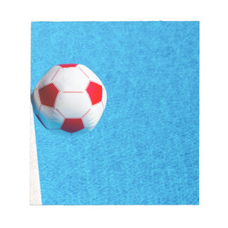 Red-white beach ball floating  in swimming pool notepad