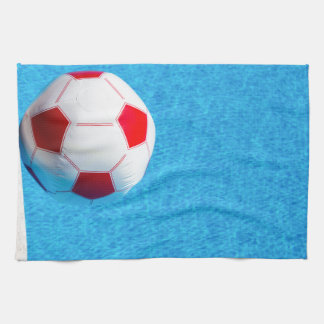 Red-white beach ball floating  in swimming pool tea towel