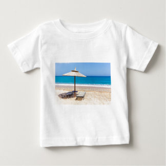Reed beach umbrella with loungers on beach at sea. baby T-Shirt