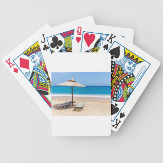Reed beach umbrella with loungers on beach at sea. bicycle playing cards