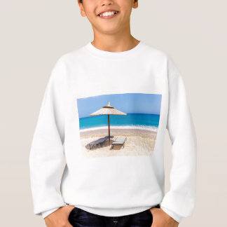 Reed beach umbrella with loungers on beach at sea. sweatshirt