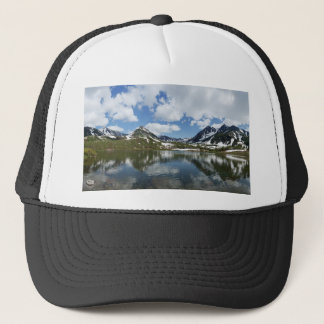 Reflection of sky and clouds in mountain lake trucker hat