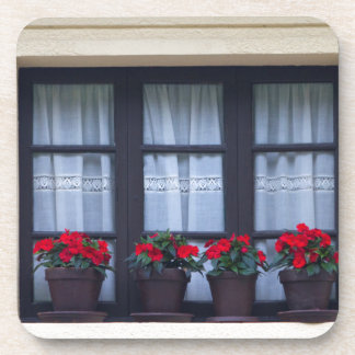 Residential housing with flowers in windows drink coasters