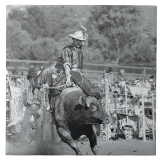 Rider hanging on to bucking bull 2 large square tile
