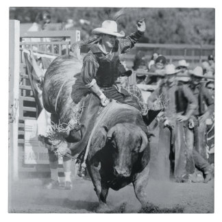 Rider hanging on to bucking bull large square tile