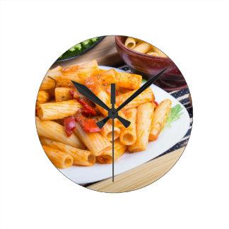 Rigatoni pasta, seasoned with pepper and arugula round clock