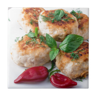 Rissole of minced chicken on a white plate tile