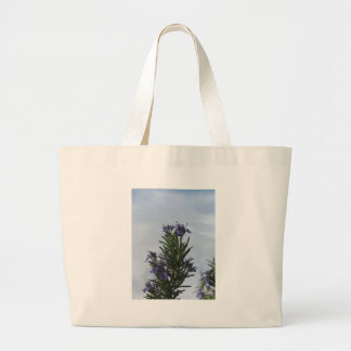 Rosemary plant with flowers against the sky large tote bag