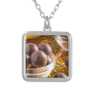 Round candy chocolate close-up on a colorful silver plated necklace