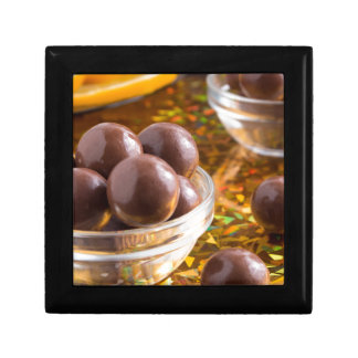 Round candy chocolate close-up on a colorful small square gift box
