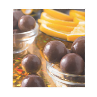 Round candy  from chocolate close-up on a colorful notepad