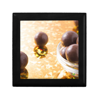 Round chocolate candy in small glass cup on color gift box