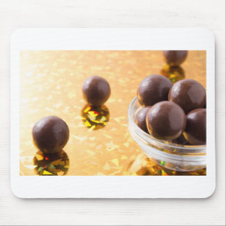 Round chocolate candy in small glass cup on color mouse pad