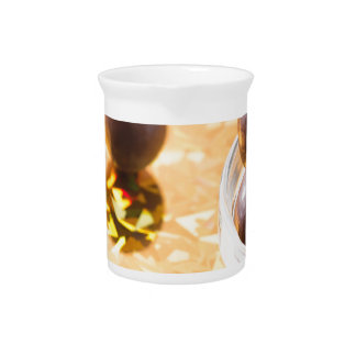 Round chocolate candy in small glass cup on color pitcher