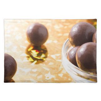 Round chocolate candy in small glass cup on color placemat