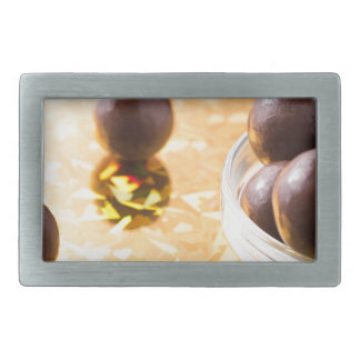 Round chocolate candy in small glass cup on color rectangular belt buckles