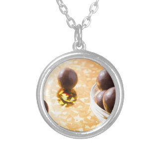 Round chocolate candy in small glass cup on color silver plated necklace