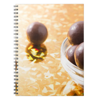 Round chocolate candy in small glass cup on color spiral notebook