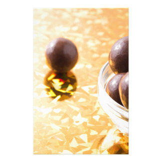 Round chocolate candy in small glass cup on color stationery