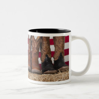 Row of cowboy boots on haystack Two-Tone coffee mug