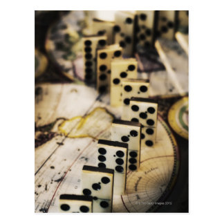 Row of dominoes on old world map postcard