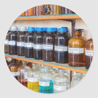 Rows of fluid chemicals in bottles at chemistry classic round sticker