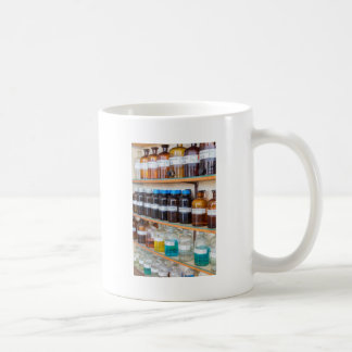 Rows of fluid chemicals in bottles at chemistry coffee mug