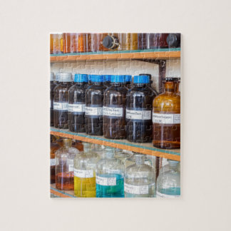 Rows of fluid chemicals in bottles at chemistry jigsaw puzzle