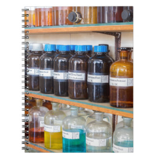 Rows of fluid chemicals in bottles at chemistry note books