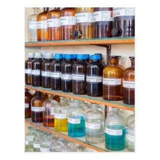 Rows of fluid chemicals in bottles at chemistry postcard