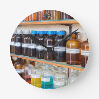 Rows of fluid chemicals in bottles at chemistry round clock