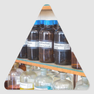 Rows of fluid chemicals in bottles at chemistry triangle sticker