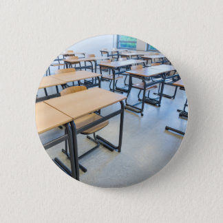 Rows of tables and chairs in classroom 6 cm round badge
