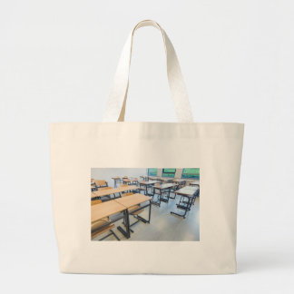 Rows of tables and chairs in classroom large tote bag