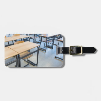Rows of tables and chairs in classroom luggage tag