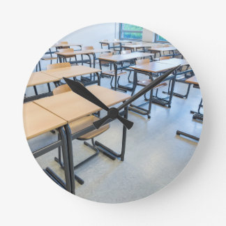 Rows of tables and chairs in classroom round clock