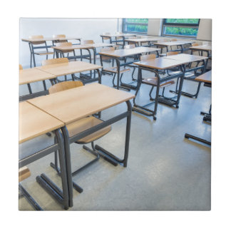 Rows of tables and chairs in classroom tile