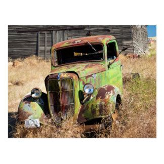 Rusting car in front of abandoned farm postcard