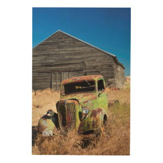 Rusting car in front of abandoned farm wood canvases