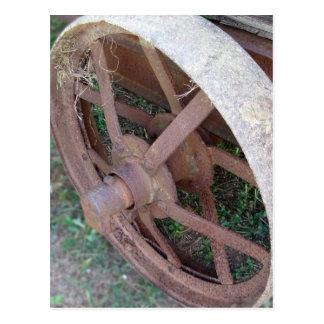 Rusty iron wheel of old cart postcard