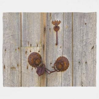 Rusty vintage old iron padlock on a wooden door _. fleece blanket