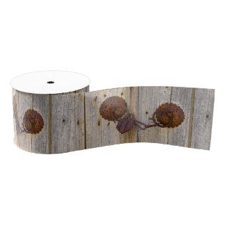 Rusty vintage old iron padlock on a wooden door grosgrain ribbon