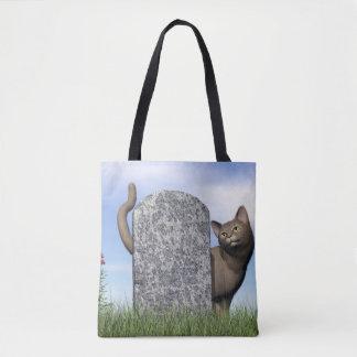 Sad cat near tombstone tote bag