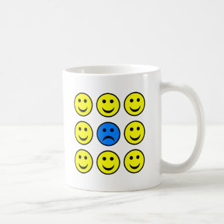 Sad Smiley Face in a Crowd of Happy Smilies Coffee Mug