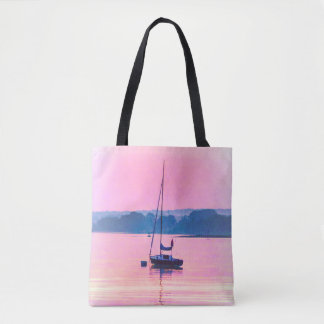 Sailboat floating in early morning light. tote bag